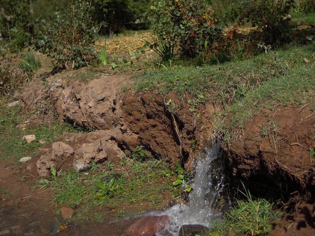 Berber leiten Wasser mit Kanaelen aus Lehm zu den Feldern.