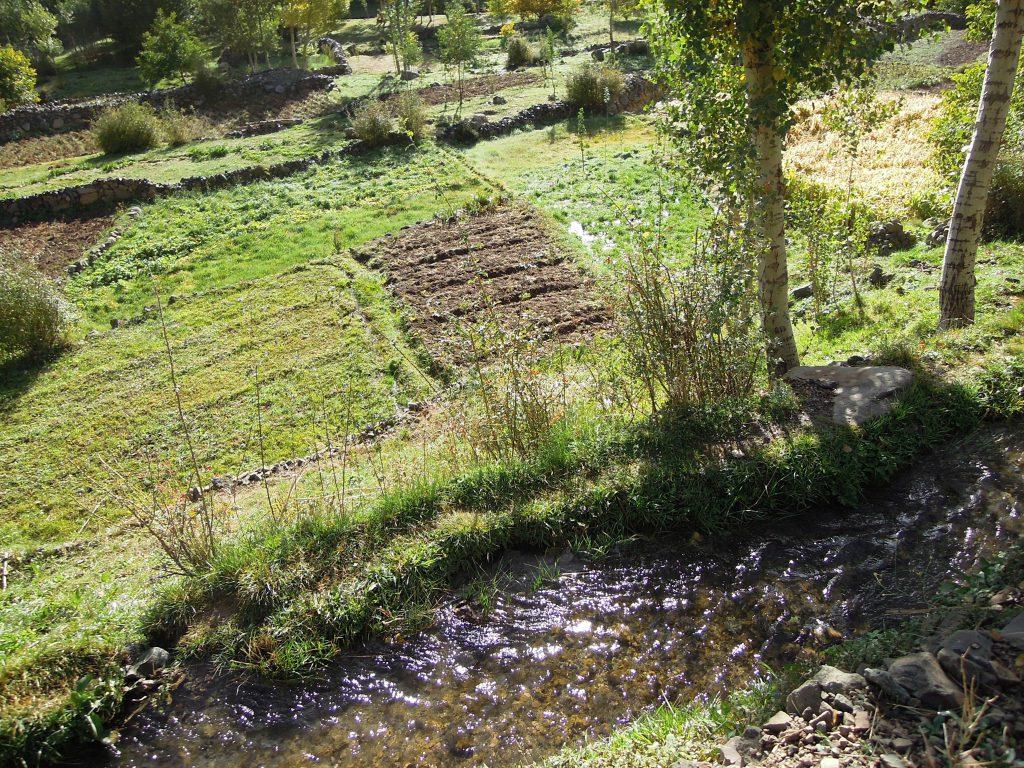 Wasser rinnt entlang eines Flusstals im Hohen Atlas